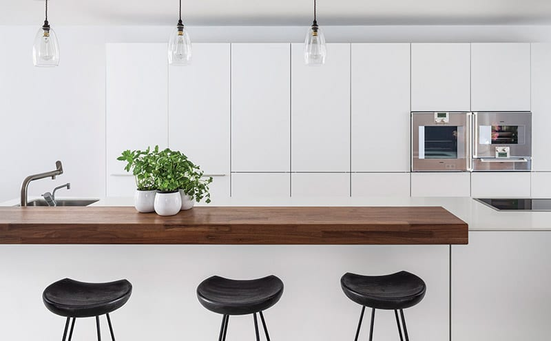 Bar stools from Rockett St George at the walnut-edged island. Note the pair of Gaggenau ovens built in to the wall of Bulthaup units – they are the only appliances on display