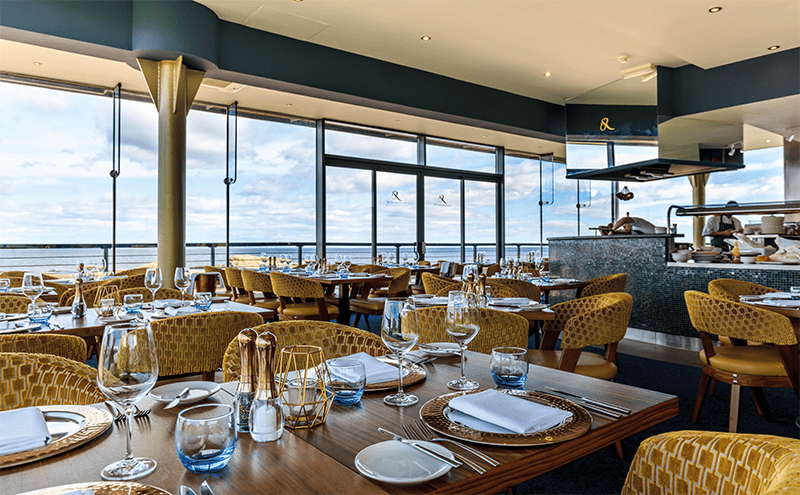 Low-backed gold chairs allow everyone to enjoy the sea views, while iridescent tiles and notes of blue add to the marine feel of the dining room