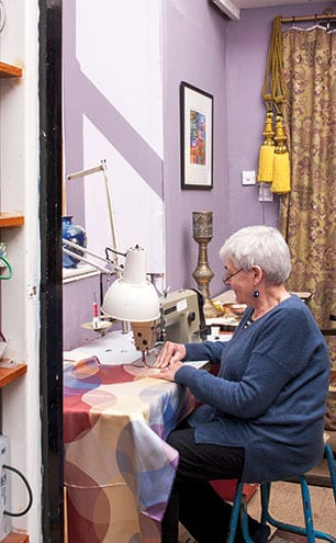 Seamstress Pip is kept busy at her sewing machine. The curtains behind her were made using an Etro fabric