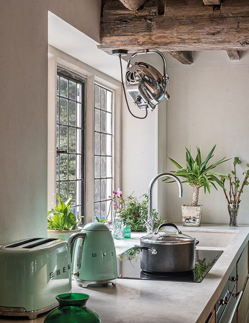 A vintage 1930s film light fixed to a beam illuminates the working area in the kitchen