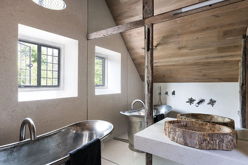 McNeill's architectural approach to design can be seen in the small bathroom, where a mirrored wall bisected by reclaimed beams cleverly magnifies the sense of space. The fossilised wood basin was sourced in Indonesia, while Italian white marble was used for the floor and wall. The bath is from William Holland. All the windows in the house were made by Bronze Casements