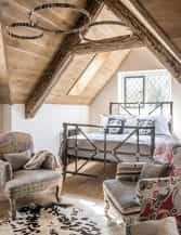 Reclaimed oak floorboards line the sloping ceiling of the guest bedroom. Vintage blue and white fabric on the bed (from And So To Bed) echoes the colours of the traditional Delft tiles which clad the chimney breast. The armchairs are upholstered in remnants of Indian prints