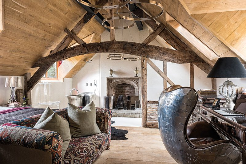 A partition wall between the bedroom and bathroom was built beneath a reclaimed cruck beam. The vintage chesterfield was reupholstered in a kilim rug bought at auction. The copper bath with tin finish is from William Holland