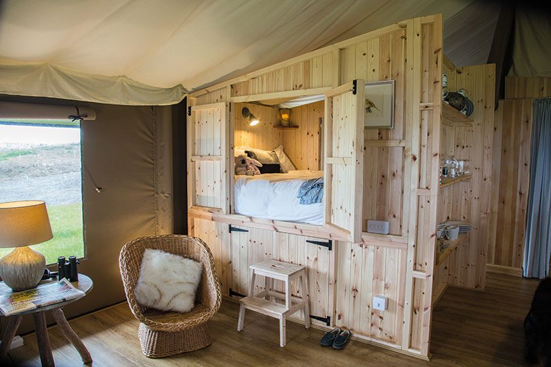The beds are from Abowed, tables and benches from Funky Chunky Furniture, cushions and throws mainly from Namaste, and bed quilts from Molly Mahon. Most of the lighting is from Garden Trading, while lanterns and candle holders are from Coach House and the antler table lamps are from Next