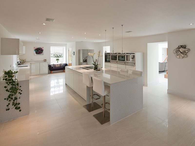 The owners chose a minimalist, pared-back kitchen from Kitchens International. Glossy tiles and work surfaces amplify the light that filters through from the adjacent atrium