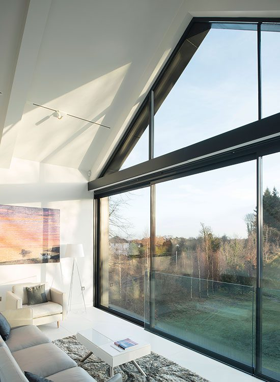 Inside the floating element is the master suite – a sitting room with a mezzanine bedroom – that makes the most of the views. IDSystems supplied the sliding doors, Juliet balcony and angled fixed-frame gable-end glazing
