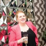 woman-in-pink-jacket-in-front-of-geometric-mirror