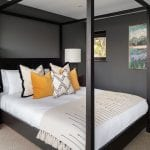 four-poster-bed-with-orange-cushion-and-white-linen