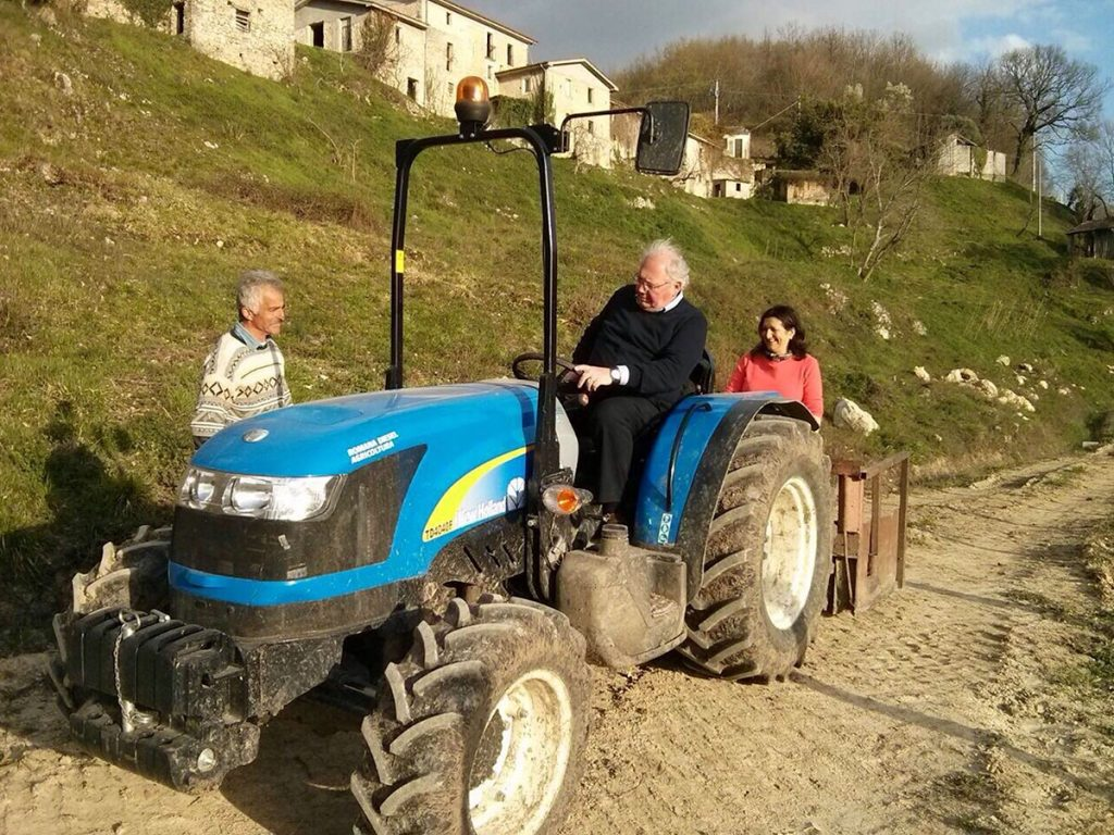 older-man-driving-blue-tractor