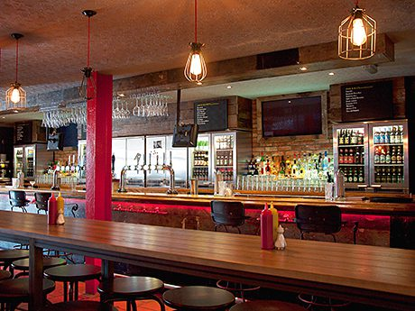 Accent lighting has been used to highlight the range of beers in the counter-top fridges and on tap. Different styles of seating have been used throughout the venue.