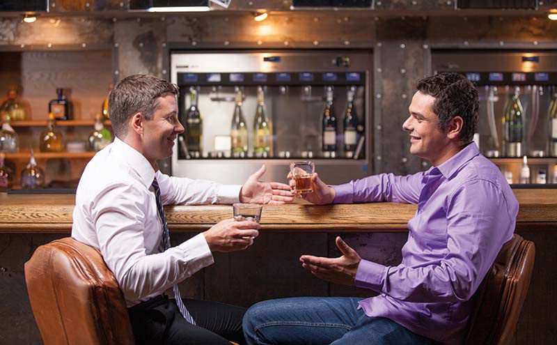 two men drinking whisky at bar