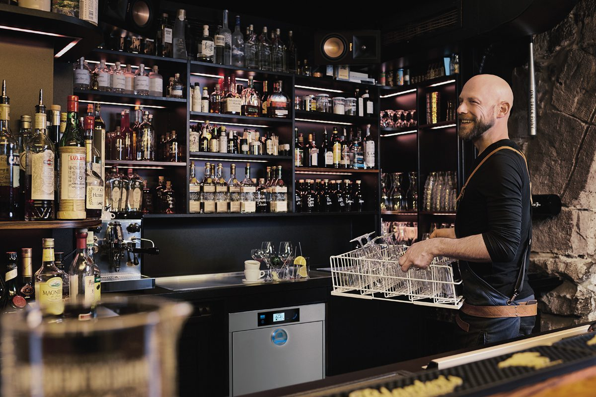 Bartender using glasswasher