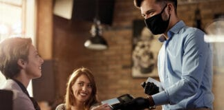 Waiter with face mask taking payment from customer