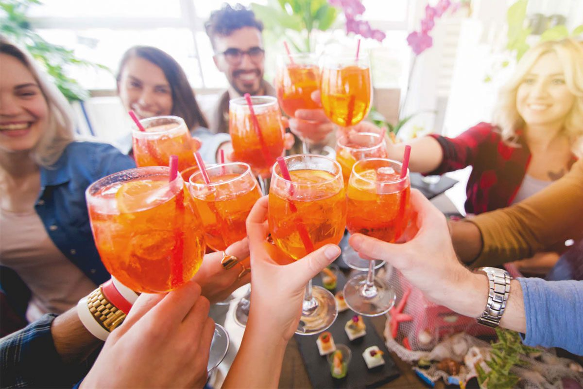A group of young people say cheers with their aperol spritz.