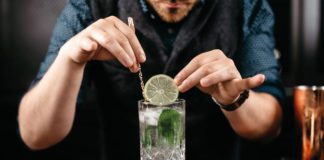 A bartender is adding a lime to a gin and tonic mix in a glass.