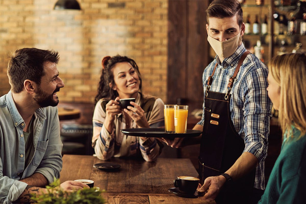 A masked waiter is serving orange juice to customers.