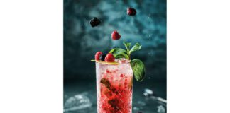 A red cocktail is on a marble table infused with berries and mint leaves.