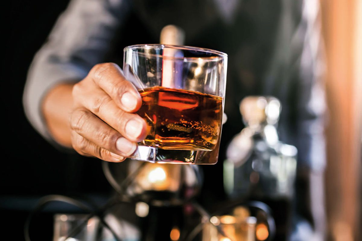 A man is holding a square glass of whiskey