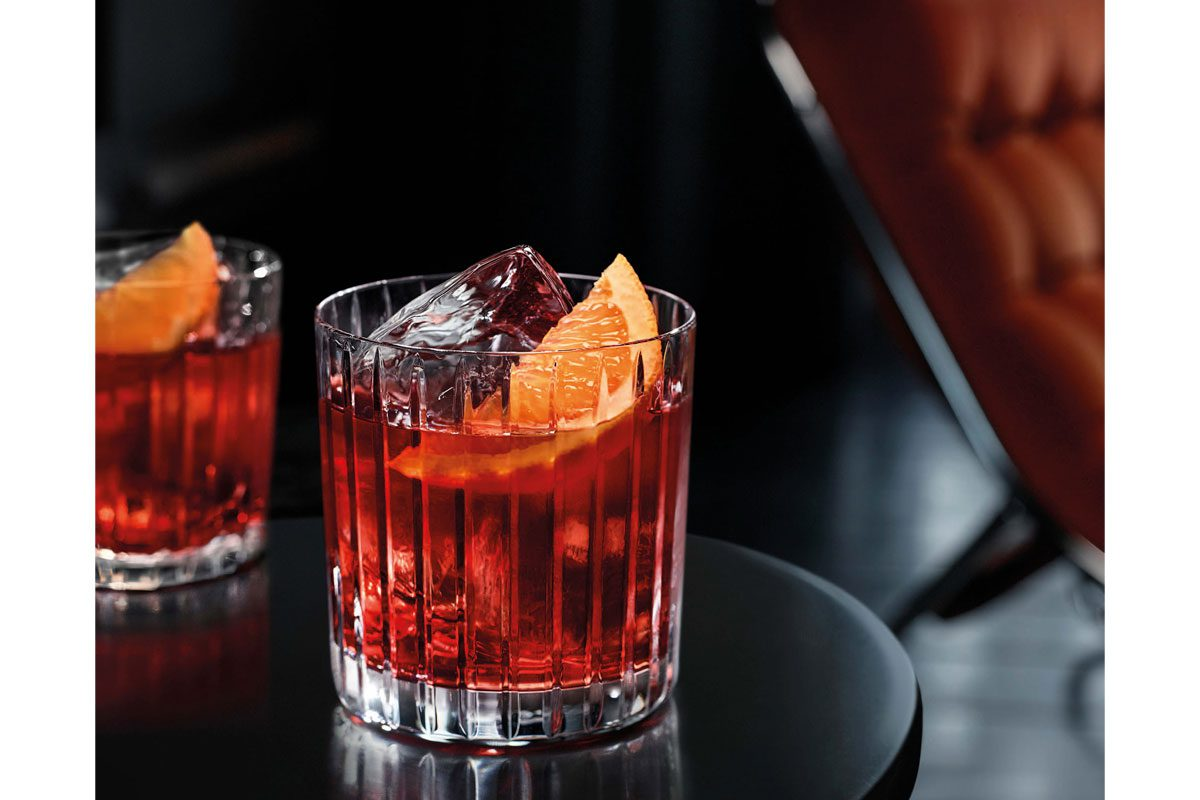 Two cocktails are sitting on a black table