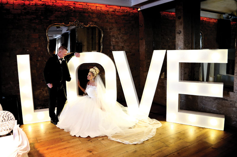 bride and groom at love letters