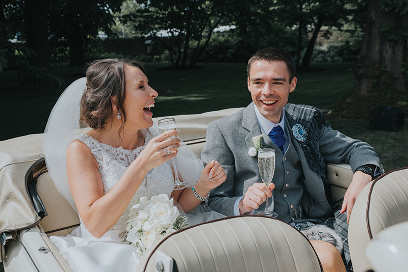 bride and groom drinking bubbles in car
