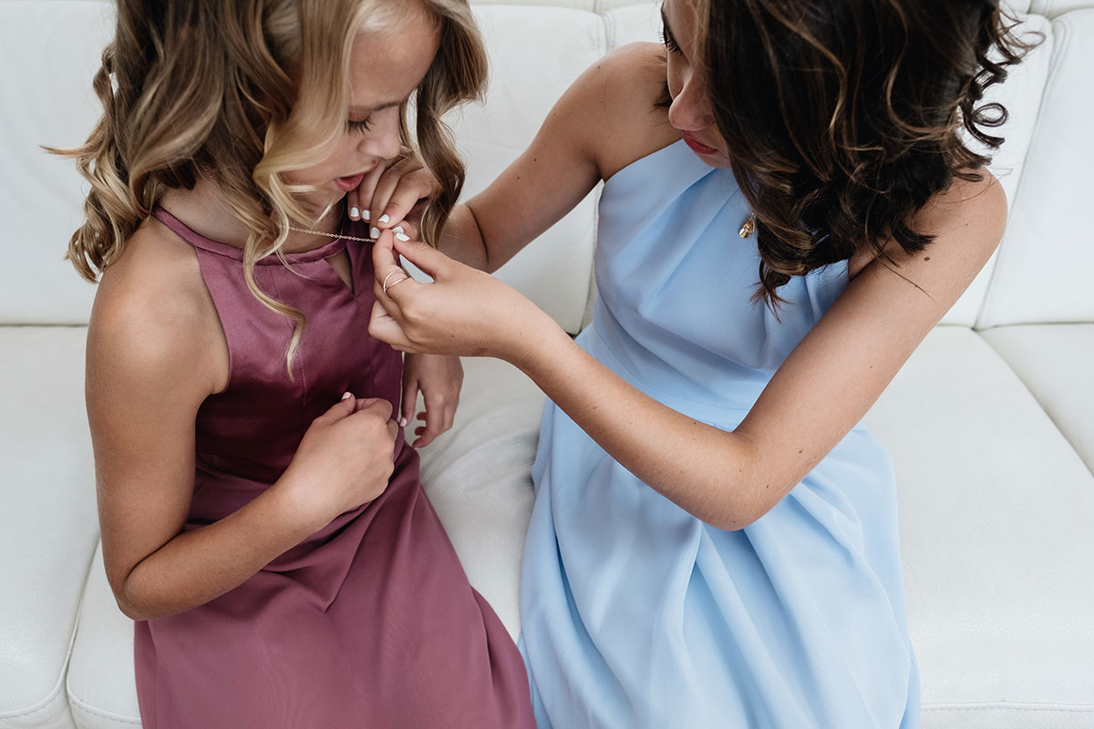 bridesmaid helping other bridesmaid put necklace on