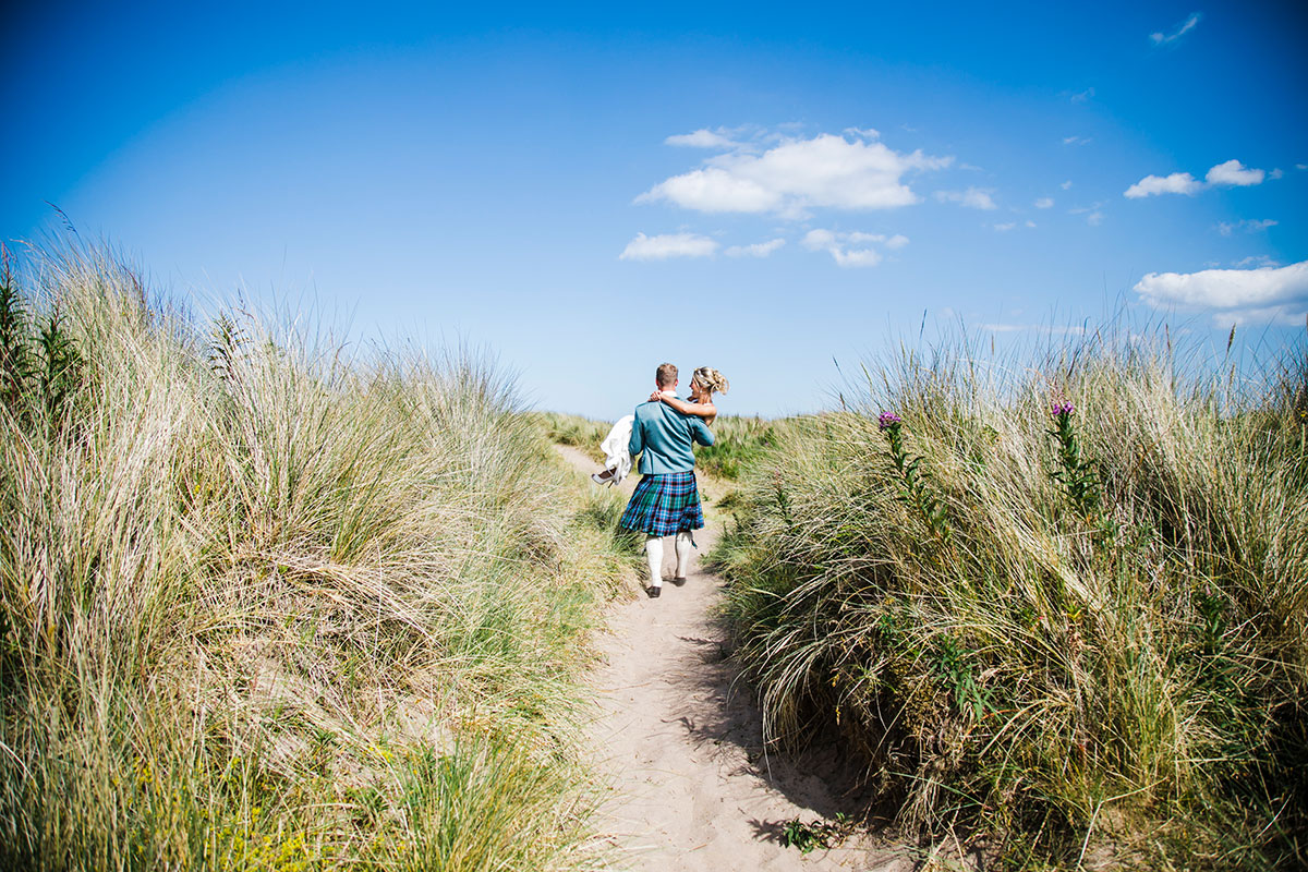 groom-carrying-bride-on-the-beach-at-Leuchars