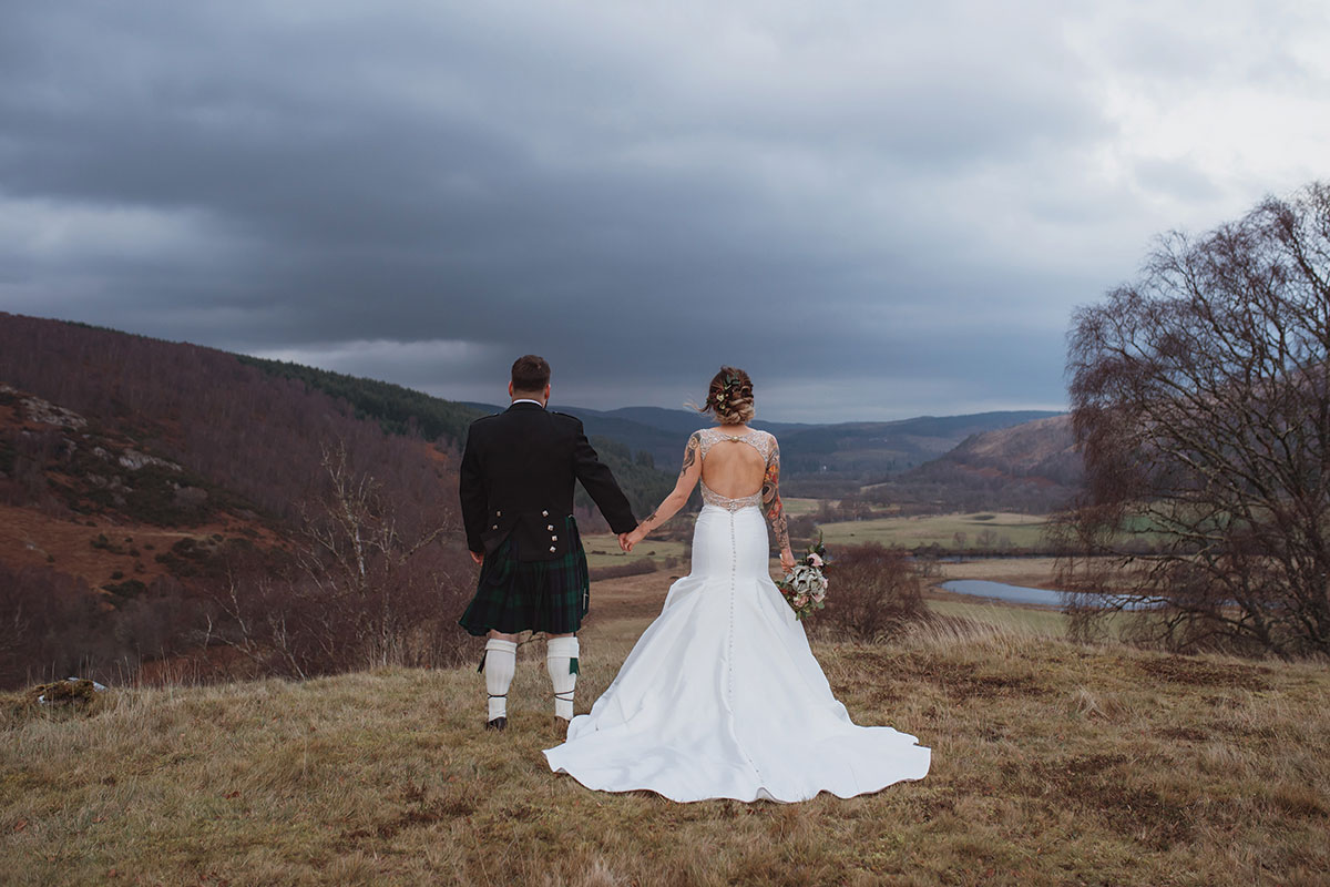 bride-and-groom-looking-out-over-scottish-landscape