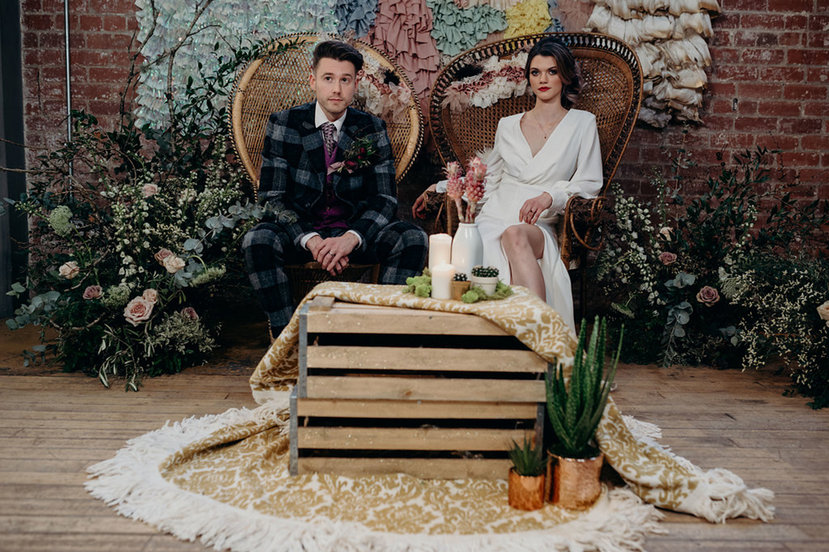 bride-and-groom-sitting-on-rattan-chair-with-rustic-styling