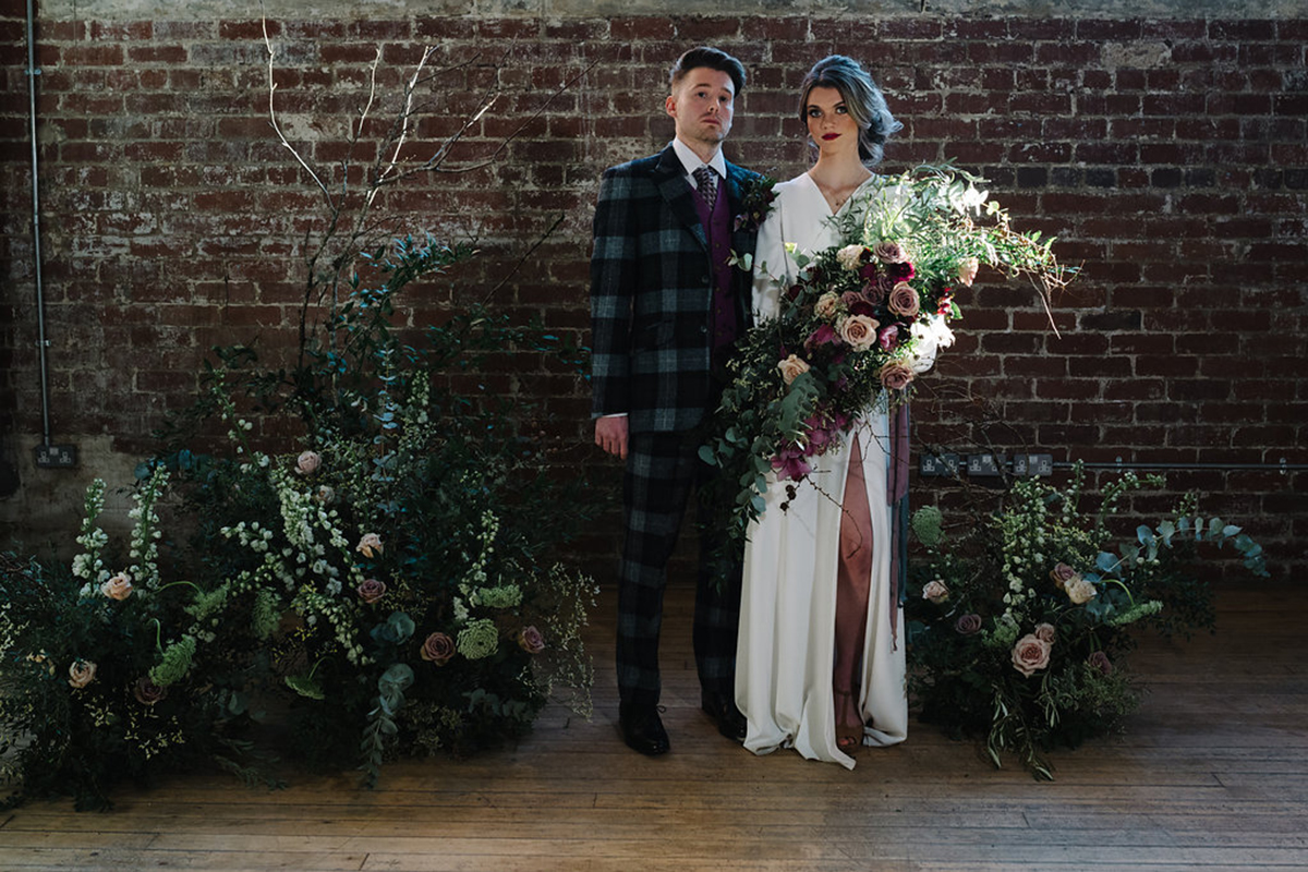 groom-in-tweed-suit-and-bride-in-white-dress-with-rustic-floral-arrangements
