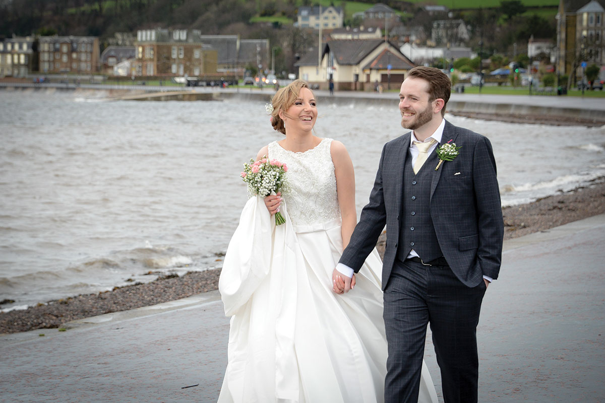 bride-and-groom-walking-by-the-sea-near-brisbane-house