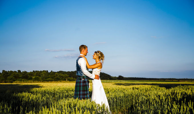 bride-and-groom-in-field-in-scotland