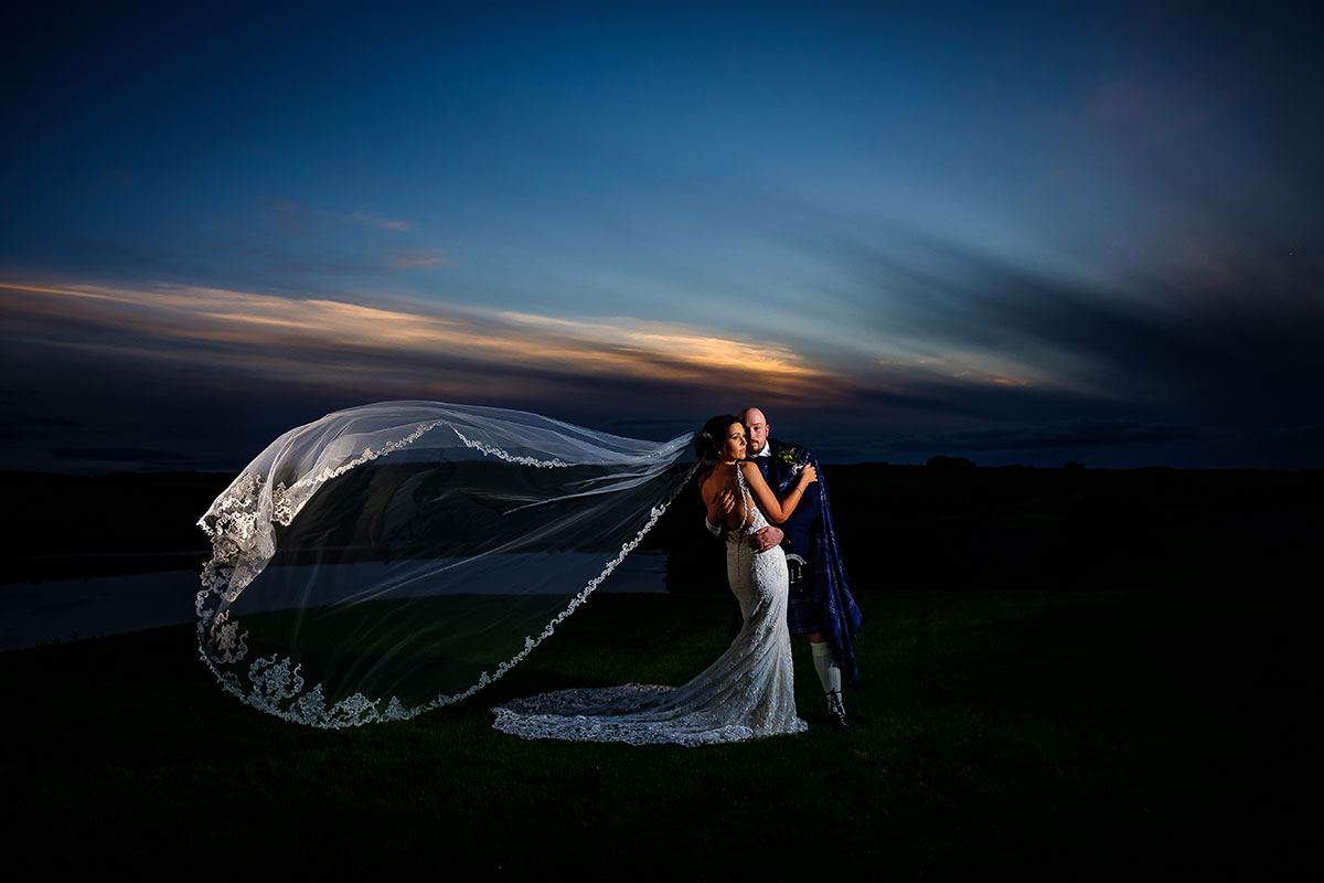 dramatic-shot-of-bride-and-groom-at-sunset-with-long-lace-veil