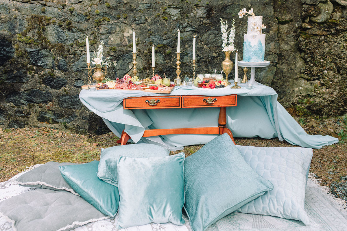 pastel-blue-cushions-and-blanket-in-front-of-dessert-table