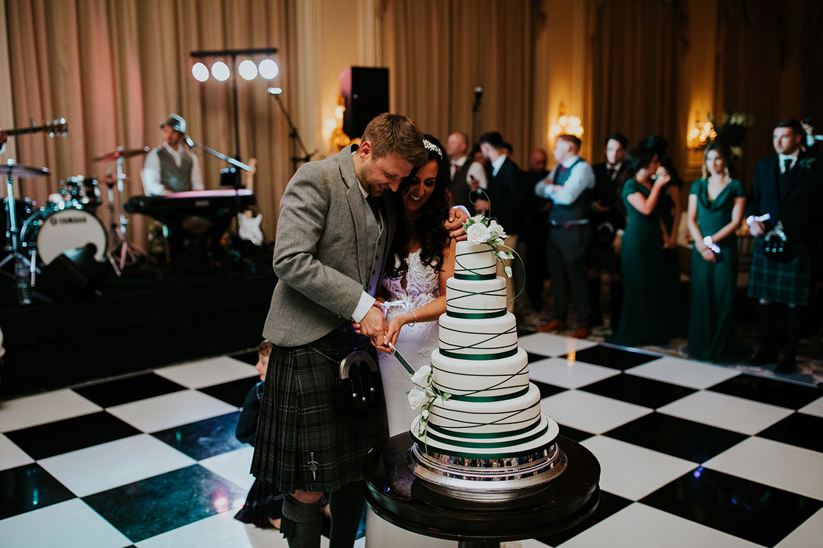 bride-and-groom-cutting-white-and-green-cake