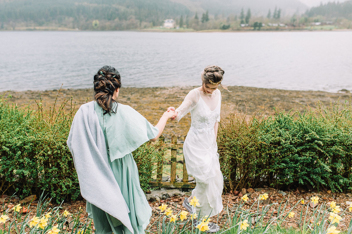 bride-holding-hand-with-bridesmaid-wearing-shawl