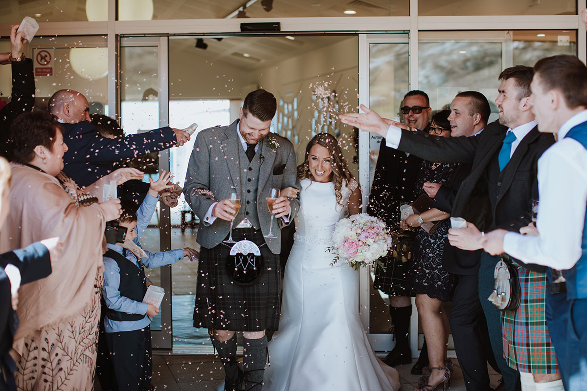 guests-throwing-confetti-on-newlyweds