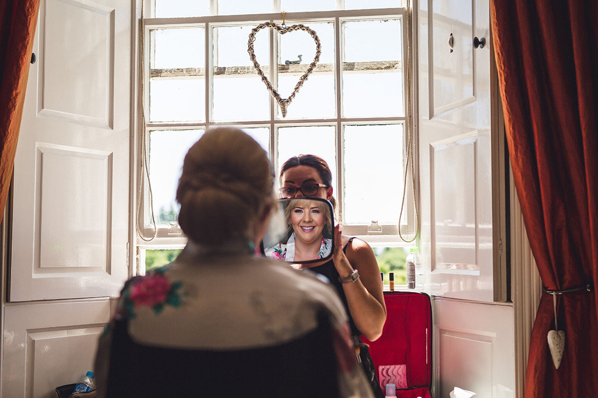 bride-looking-in-mirror-after-having-makeup-done