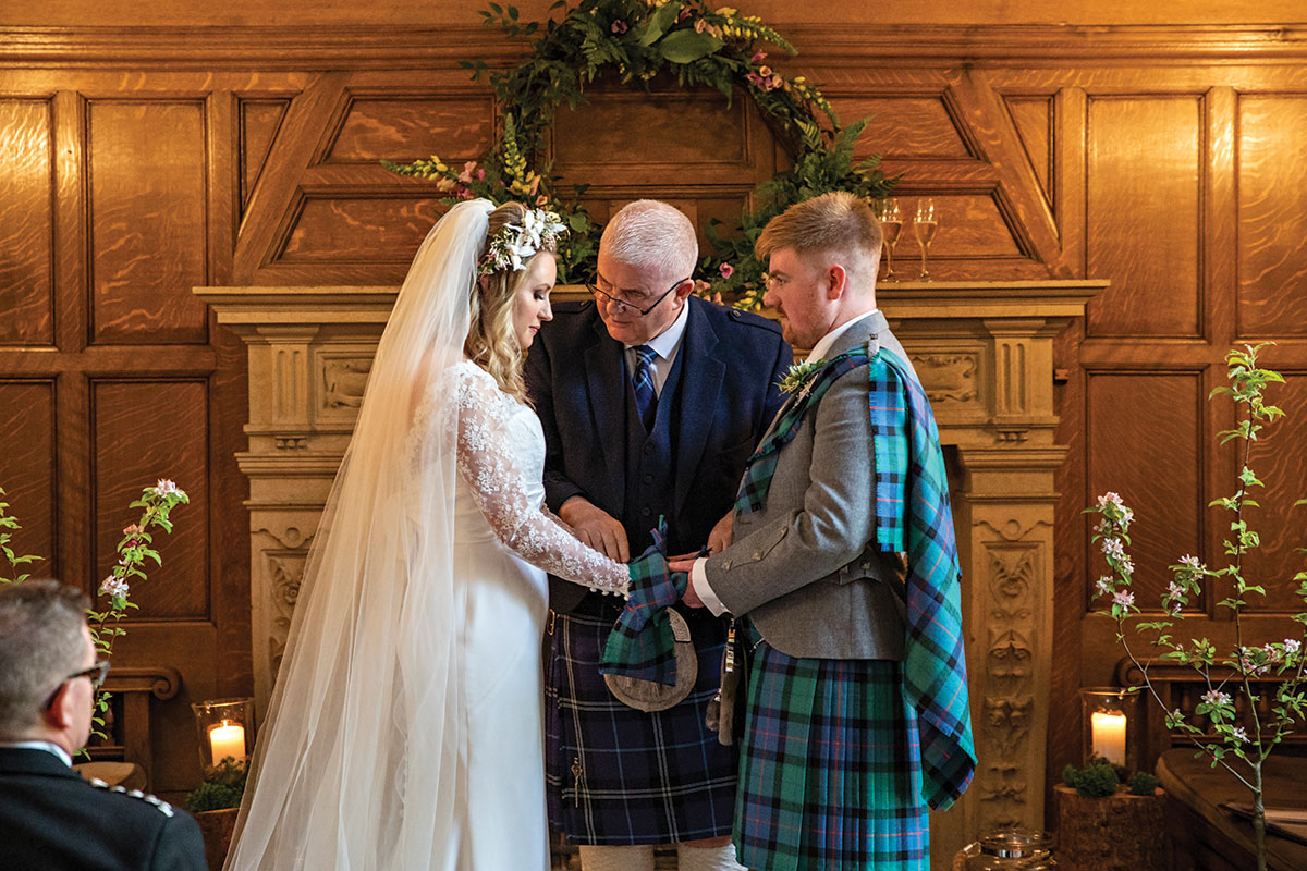 bride-and-groom-having-handfasting-during-ceremony