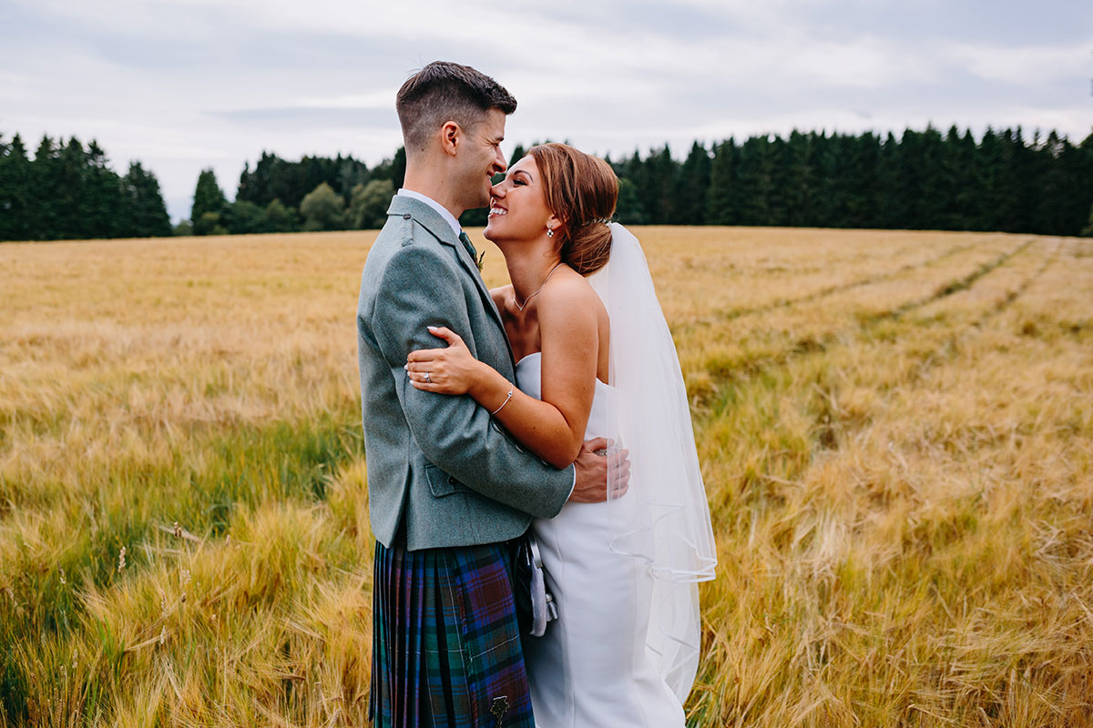 bride-and-groom-in-field-smiling-at-each-other