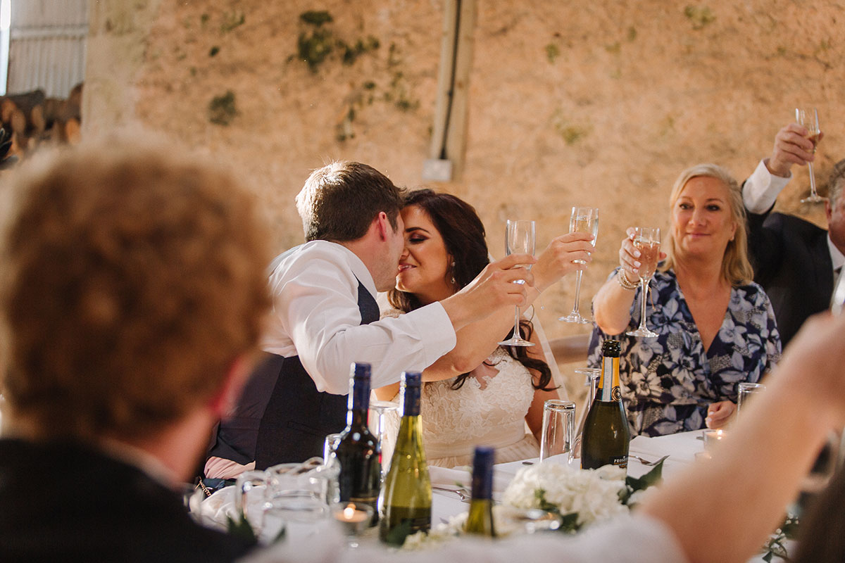 bride-and-groom-kissing-during-speeches