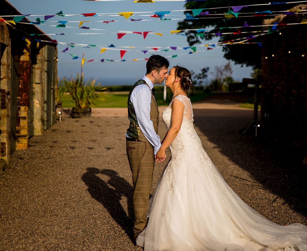 bride-and-groom-kissing-with-bunting-in-the-background