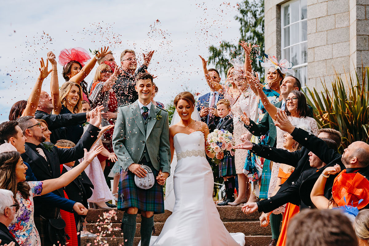 guests-throwing-confetti-on-the-couple