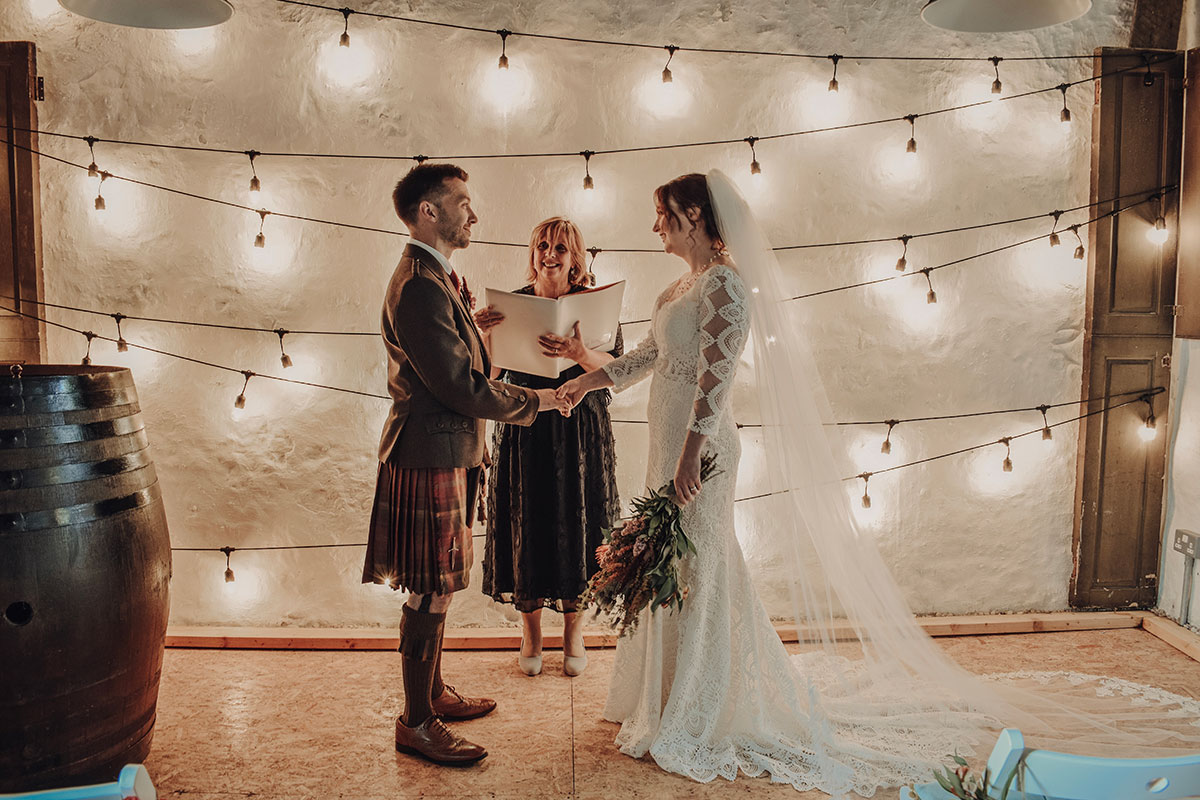 bride-and-groom-with-celebrant-inside-the-barn