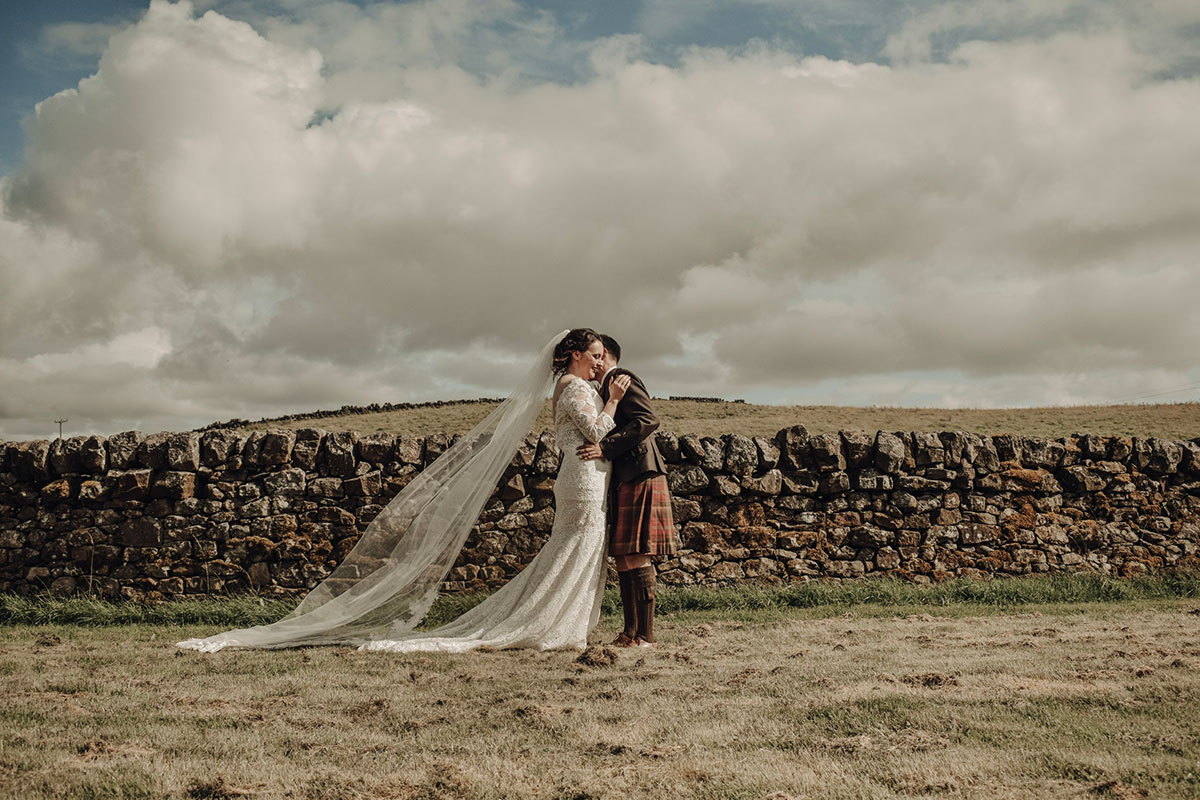 bride-and-groom-standing-on-hill-with-rolling-backdrop