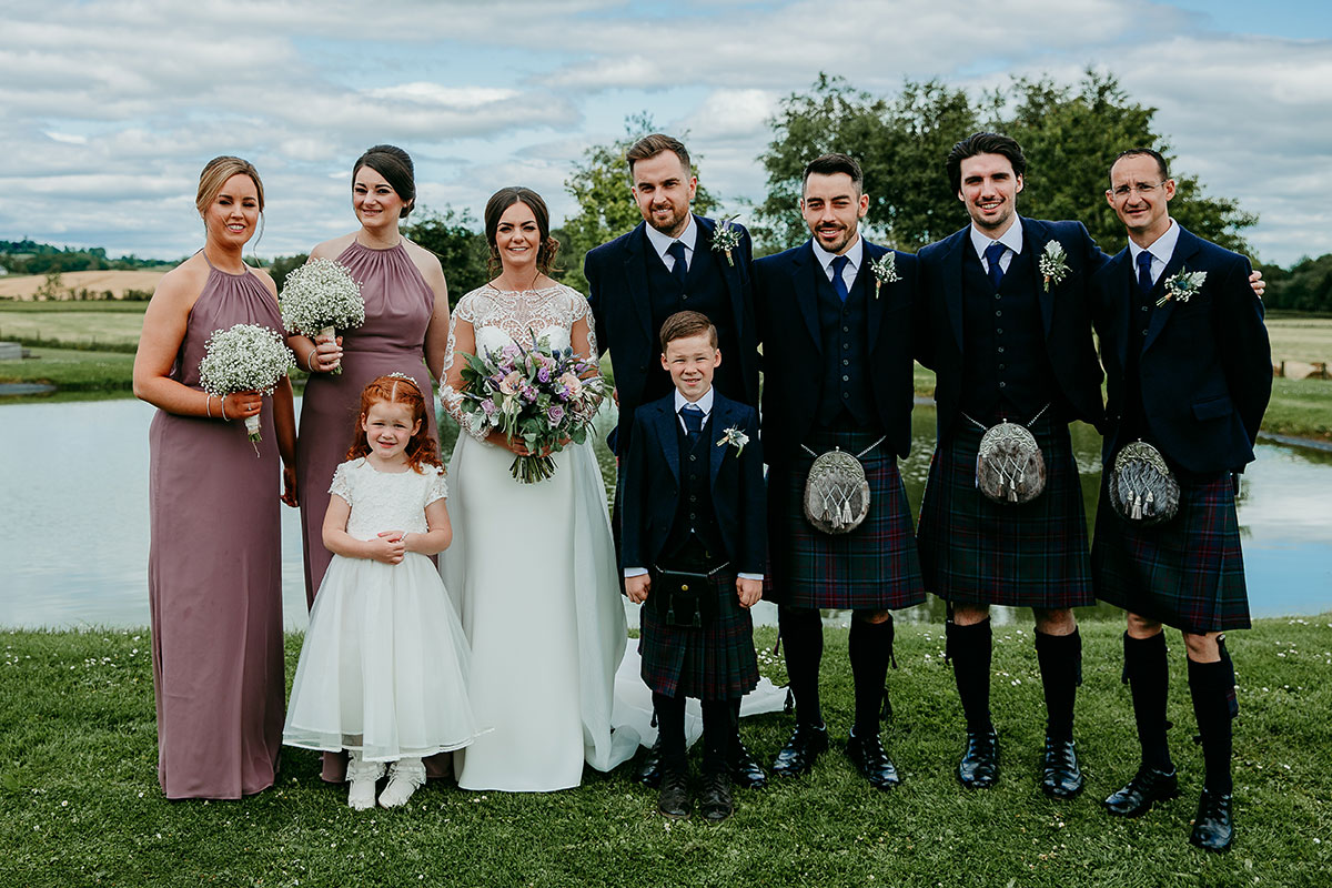 bridal-party-with-kilt-outfits-and-purple-bridesmaid-dresses