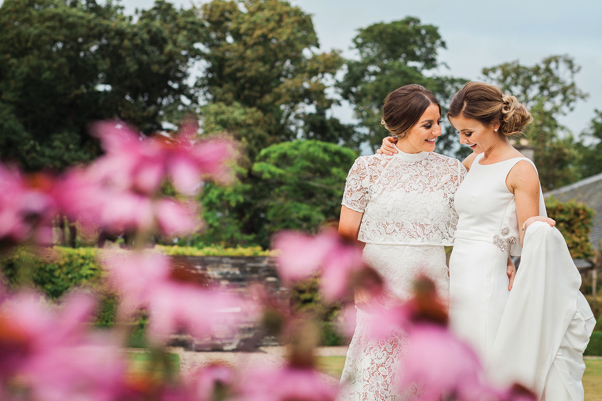 brides-with-pink-flowers-in-front-of-them