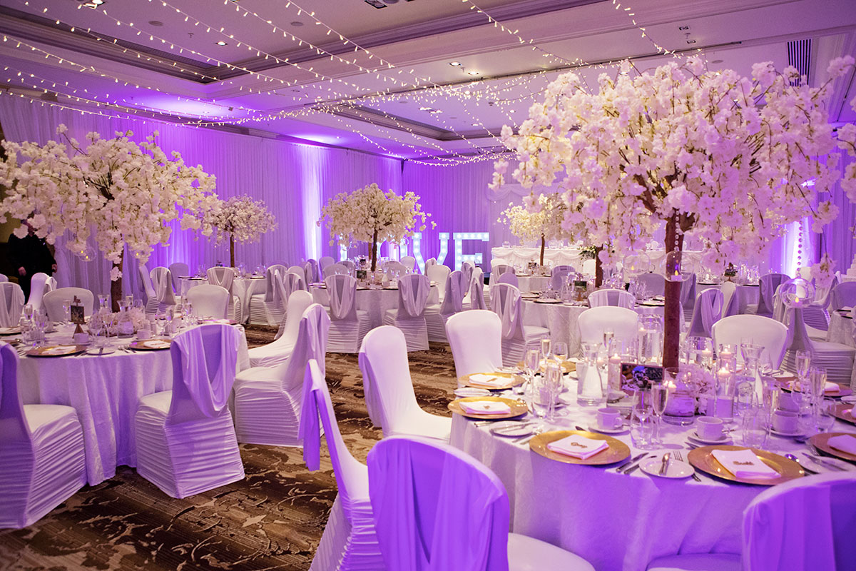 reception-room-with-colour-wash-lighting-and-cherry-blossom-centrepieces