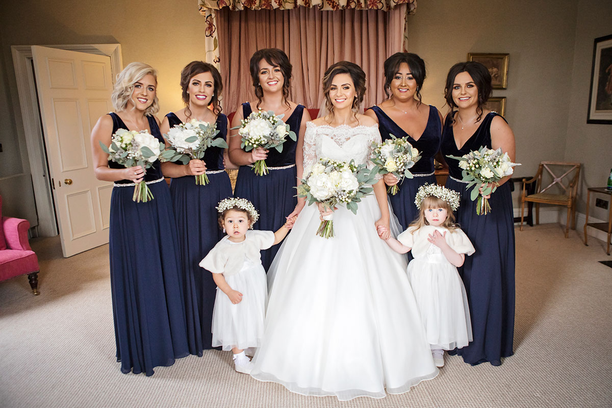 bride-and-bridesmaids-in-navy-dresses-with-wintery-flowers