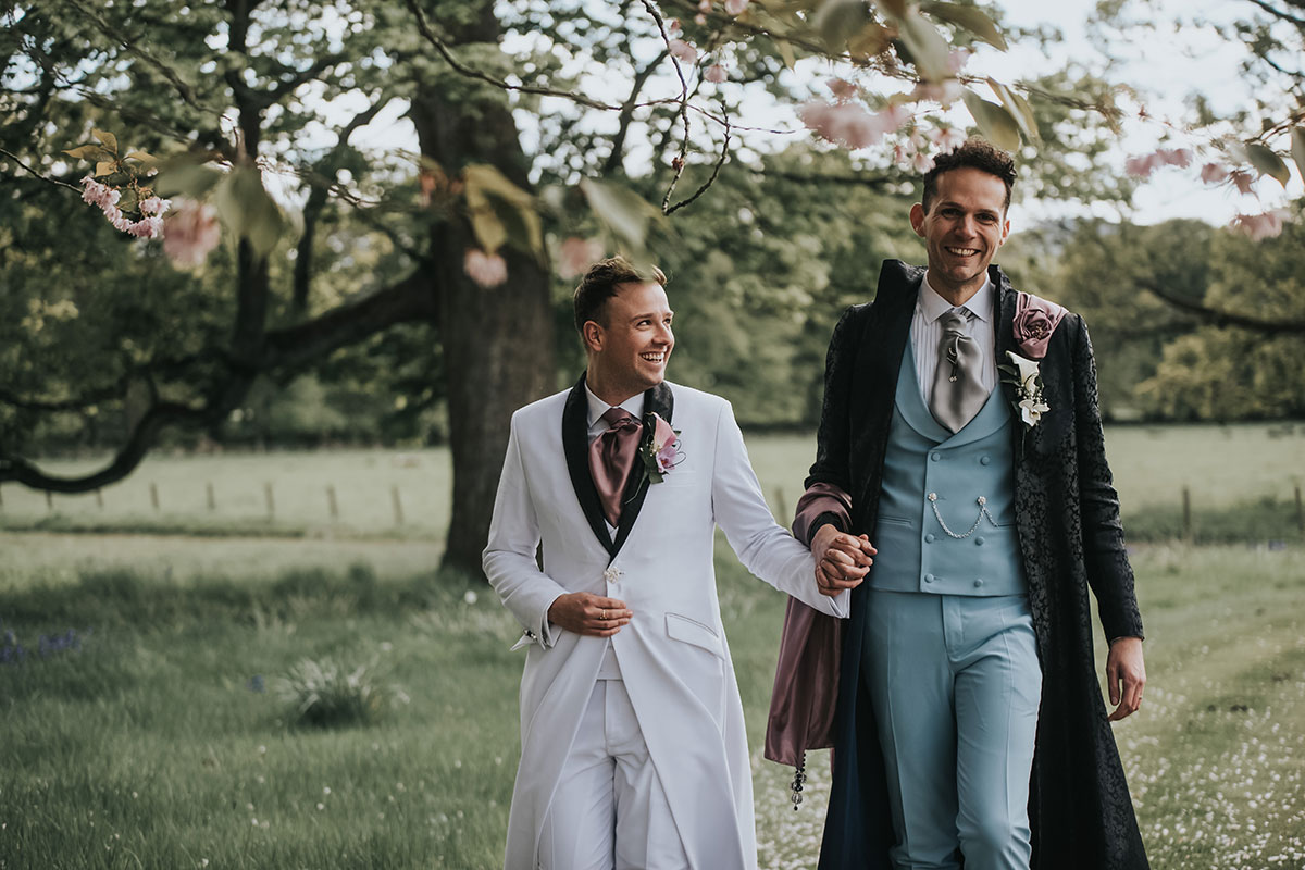grooms-in-long-suits-holding-hands